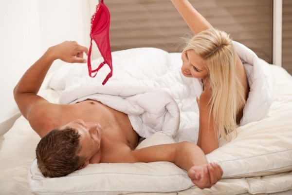 Woman tales off red knickers in bed with man