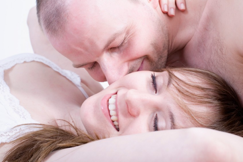 Man kisses woman on neck as she lies in bed