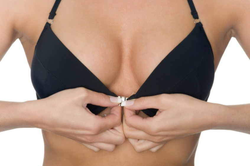 Woman unclipping bra from the front
