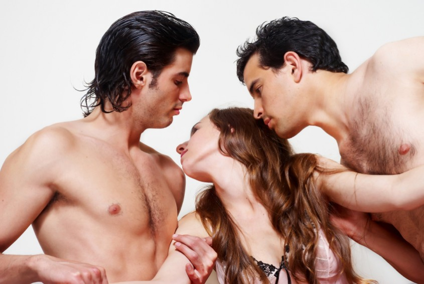 two men and a woman engaging in a threesome