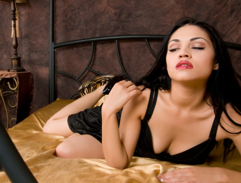 Woman in black bra leans towards the camera whilst lying on bed