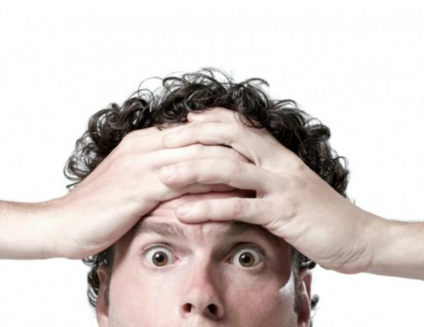 Man holds head looking shocked