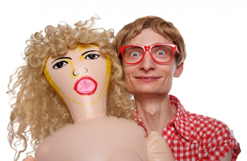 Man with glasses stands next to a blow up doll!