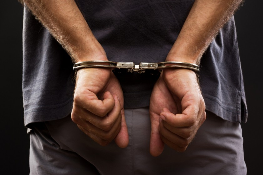 Man with hands behind back in handcuffs