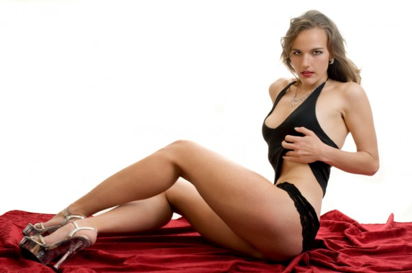 Woman in skimpy black clothing sat on red rug