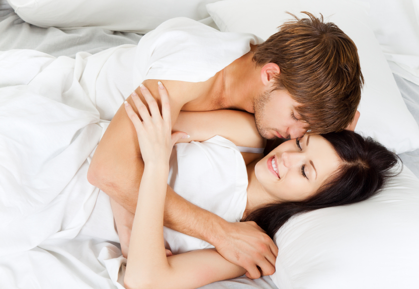 Man and woman snuggle in bed