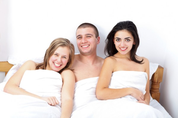 Man in the middle of two women in bed