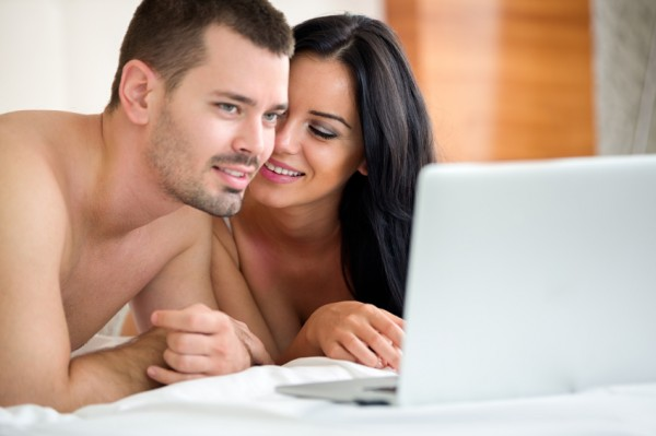 Man and woman look at a laptop