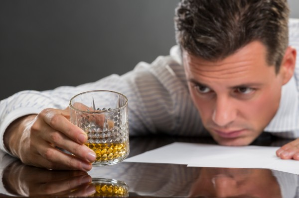 Man with head on table looks at shot of whiskey