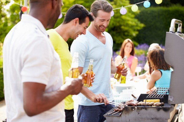 Group Of Men Cooking On Barbeque At Home