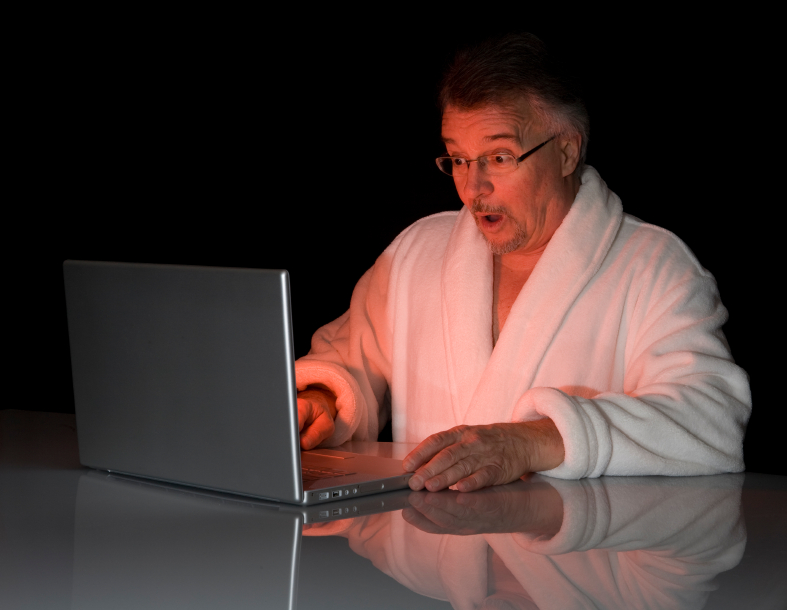 Man in bathrobe looks at laptop