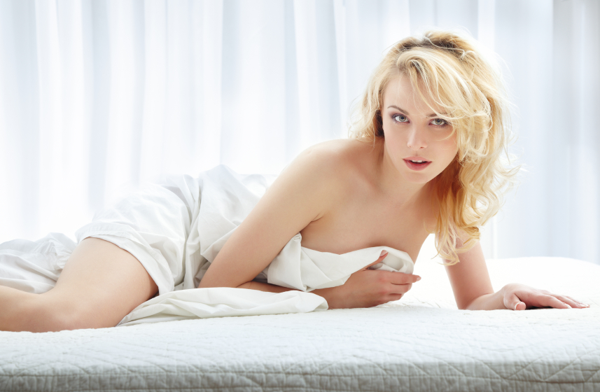 Sexy lady laying on the bed and covered by the blanket