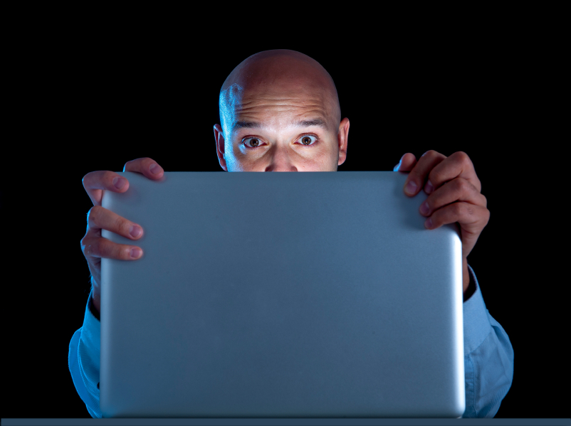 man looks at laptop