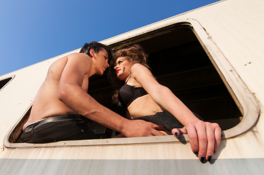 half naked man and a woman at open train window