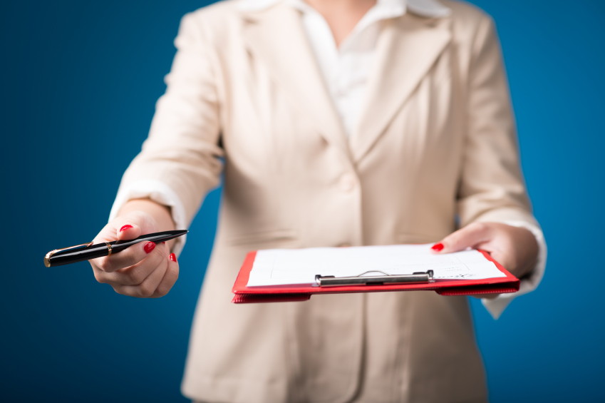 A woman in a suit stands with a clipboard