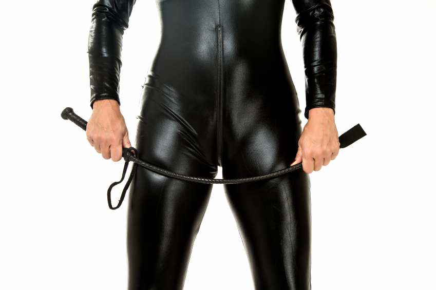 A woman in a black latex suit is holding a fetish whip made of leather in her hands.