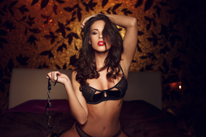 Sexy woman kneeling and holding handcuffs on bed, bdsm