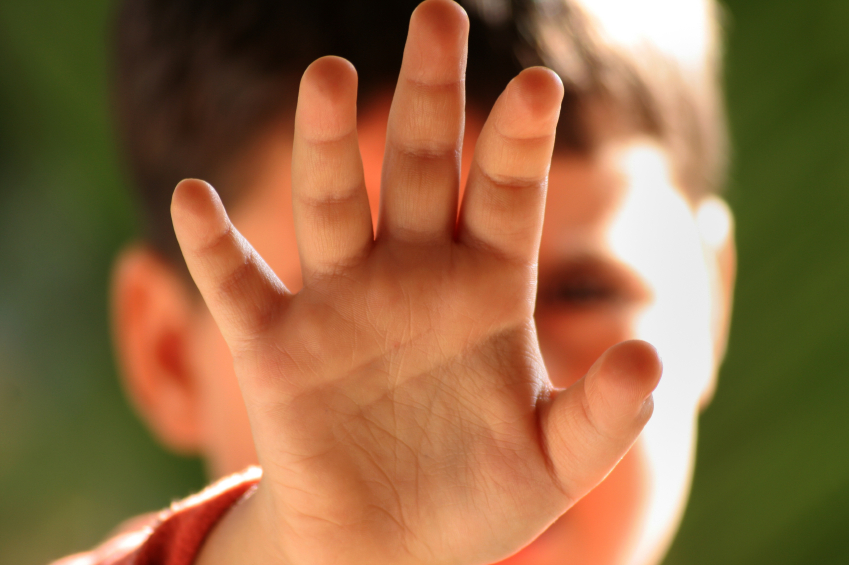 Child with hand in front of face
