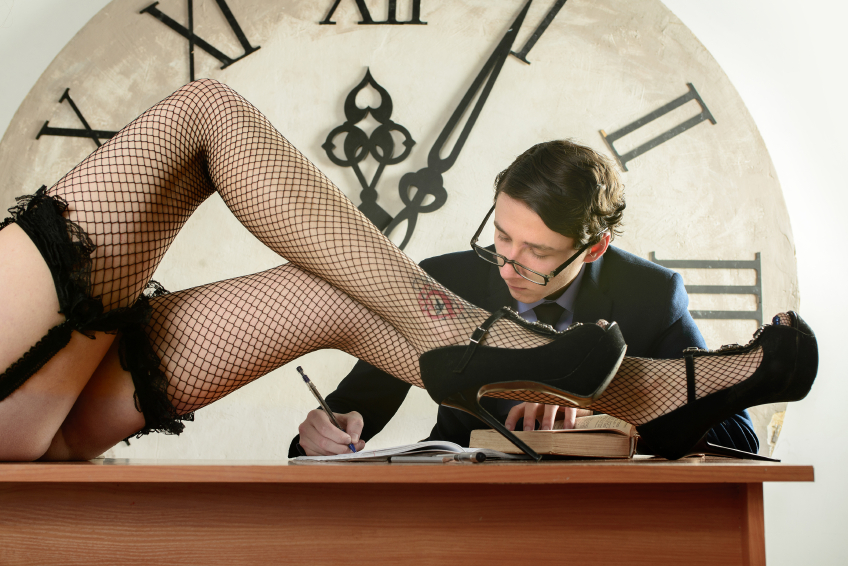 Sexy long legs in pantyhose in front of Man studying and take notes late at night. Concentrated student studying at his desk. girl Friday is on the table in front of man