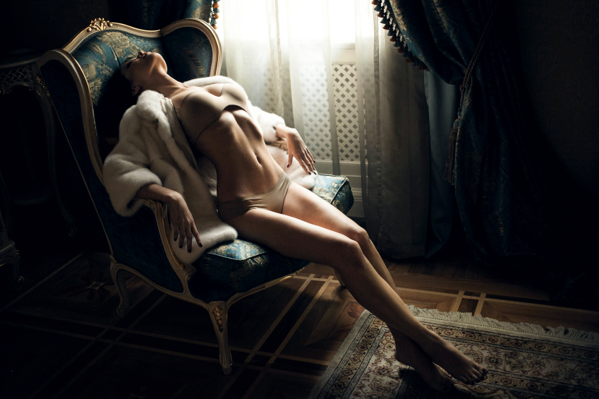 Young girl in lingerie and fur coat, sexy sitting in a chair by the window
