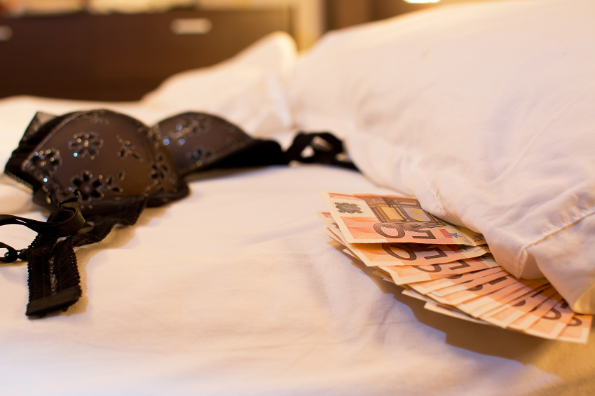 Lingerie and money on a white bed sheet
