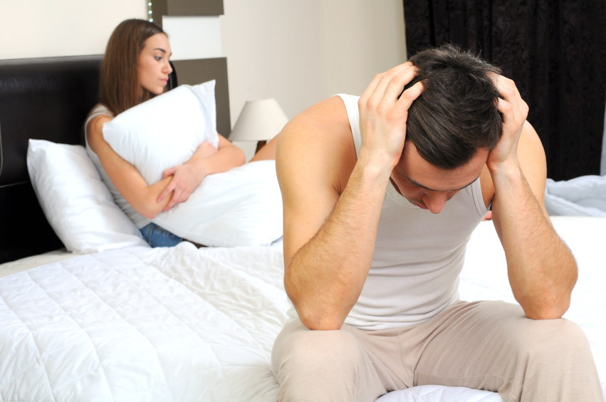 A man and woman in bed, trying to deal with premature ejaculation