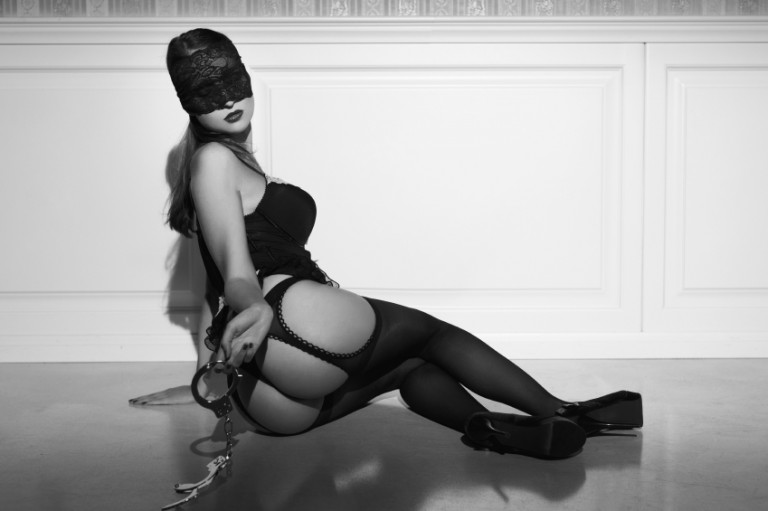 Sexy woman with handcuffs sit on floor black and white, looking like she just stepped out of 'Fifty Shades of Grey'
