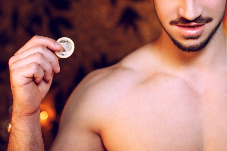 A man holds a condom he has gotten from his goodie drawer
