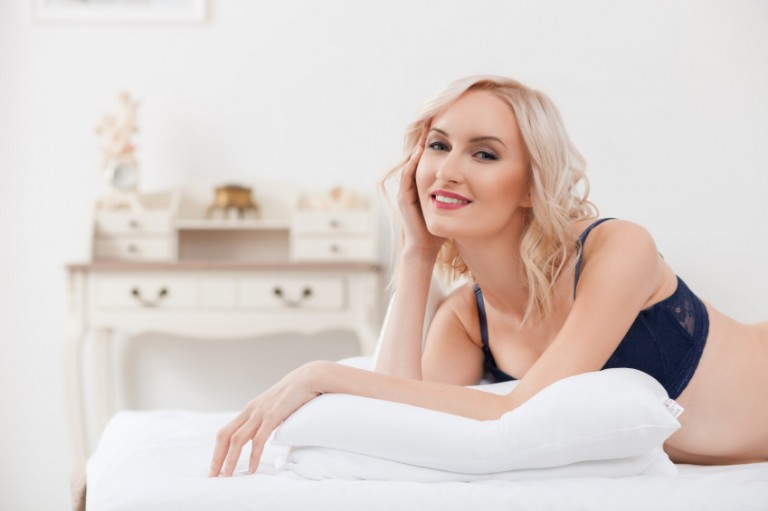 A sexy woman lying on a bed and thinking about the porn England loves