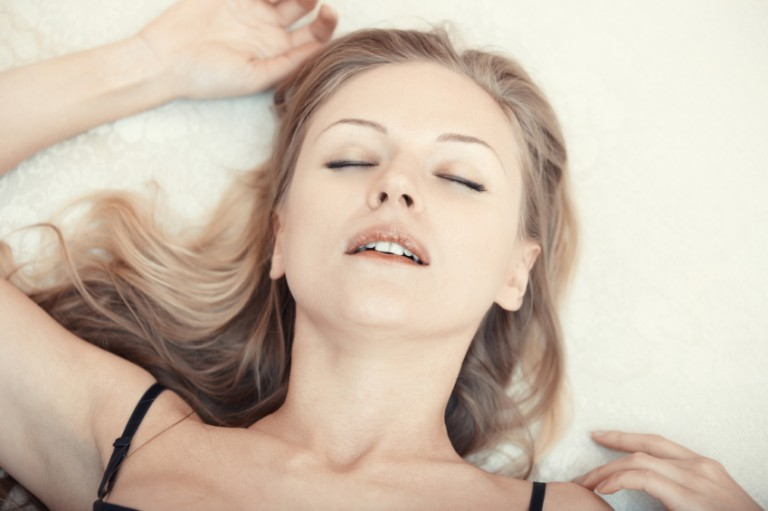 Woman lying back and having an orgasm