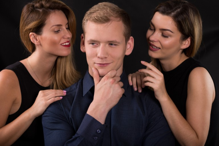 A man contemplating what it would be like to have a threesome with two sexy ladies