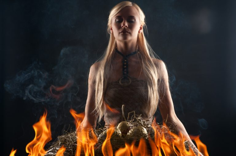 A woman stands in fire with dragon eggs, looking like Daenerys Targaryen in Game of Thrones
