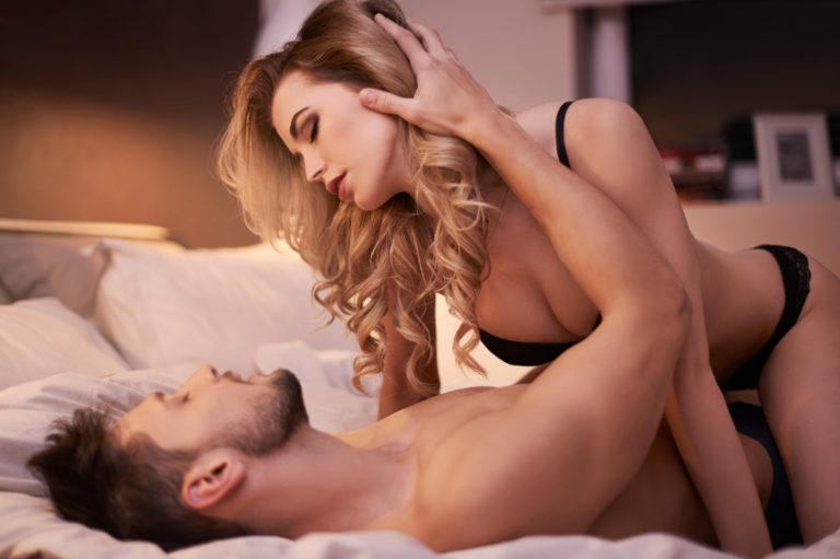 Woman on top of man in bed