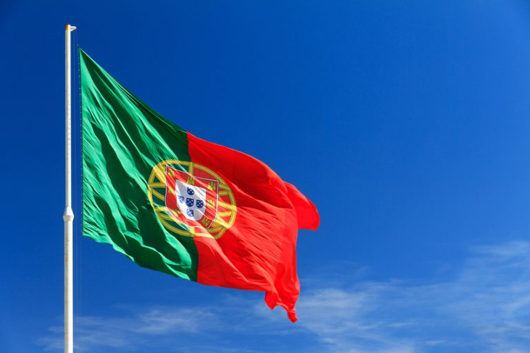 Beautiful large Portuguese flag waving in the wind against a blue background in Lisbon, Portugal