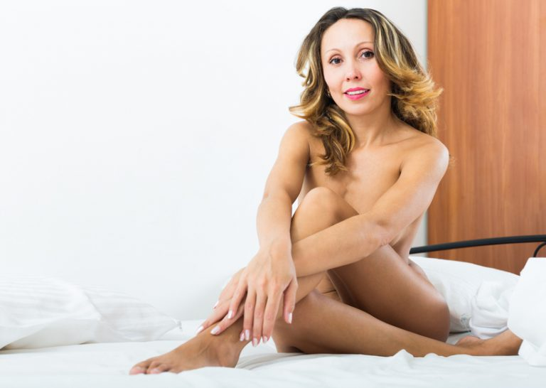 A sexy older woman posing nude on a bed, showing that mature people have better sex