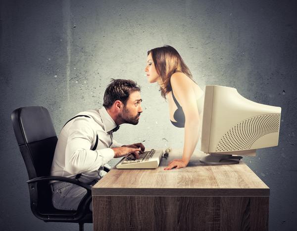 A man sits at a computer enjoying webcam sex