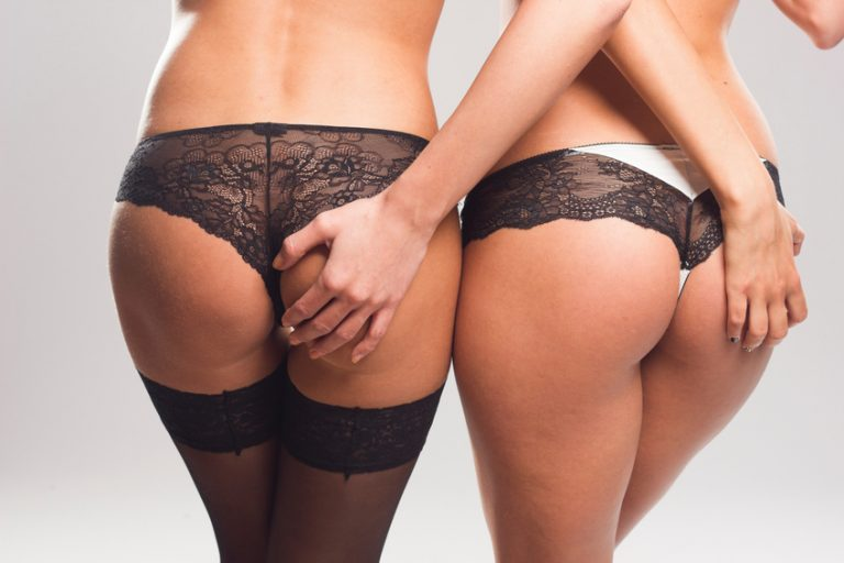 Two sexy women touching each others buttocks