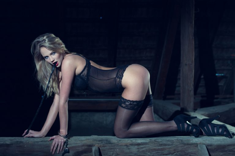 sexy blonde on knees in BDSM gear