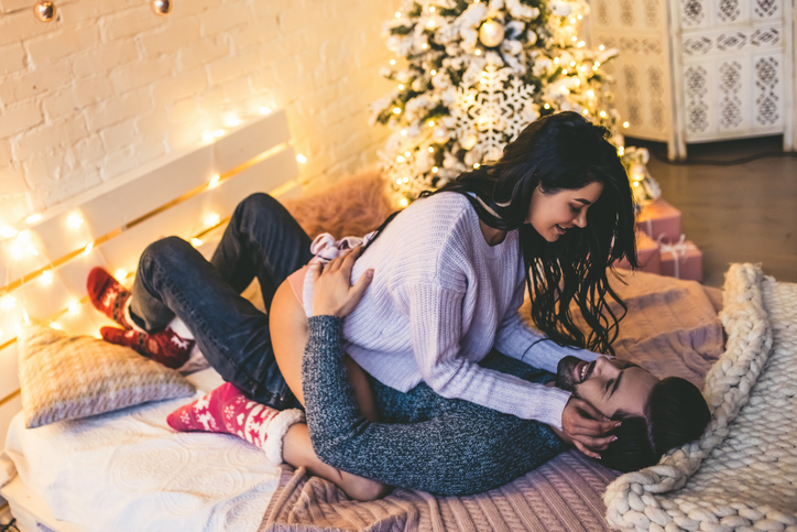 Couple cuddle underneath Christmas tree