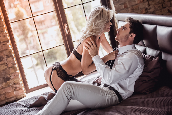 Handsome young businessman in suit and sexy young woman in black lingerie are going to have a sex