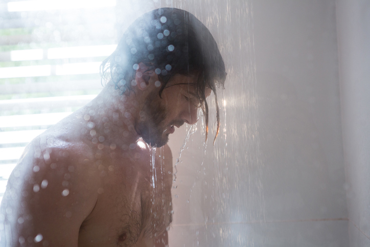 Man taking a shower in bathroom at home