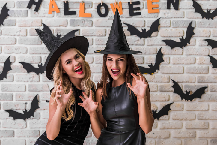 Beautiful girls in black dresses and witch hats are showing claws, looking at camera and smiling, on background decorated for Halloween
