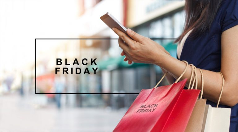 Black Friday, Woman using smartphone and holding shopping bag while standing on shopping mall background