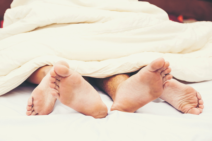 Close up of male and female feet on a bed - Loving couple having sex under white sheets in the bedroom - Concept of sensual and intimate moment of lovers - Vintage filter - Focus on male foot