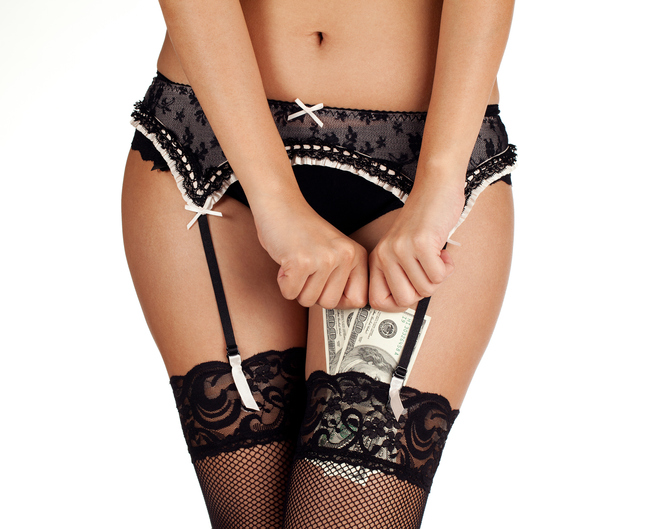 A woman in lace stockings and underwear putting money in her stockings.