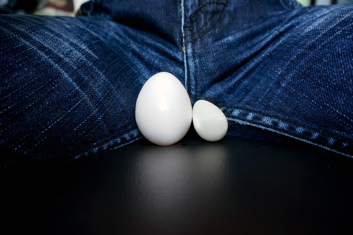 The male testicles, in the form of chicken eggs, between the legs of the guy in the jeans. Disease of male genital organs. inflamed testicles enlarged. testicular cancer
