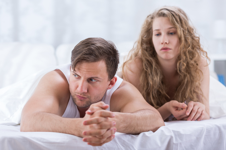 Couple is lying in bed and sad after having argument