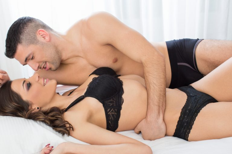 Attractive couple in bed enjoying foreplay