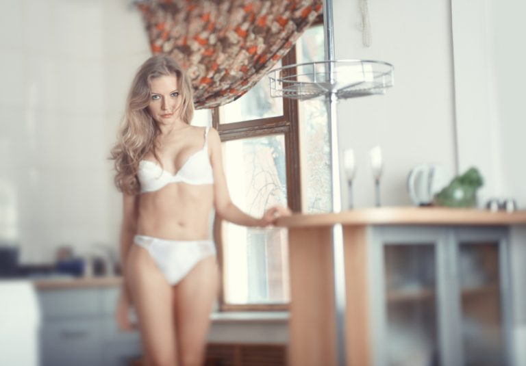 A sexy woman in lingerie stands in her kitchen, eager to have some home sex