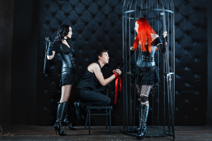 Two girls mistress dominate man. They tied him up and beat whip as punishment.